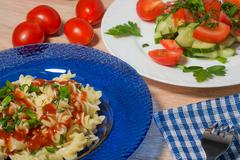 tasty pasta with vegetables and sauce in a blue plate - stock photo