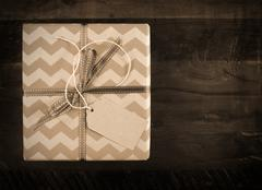 Festive gift box with chevron stripe wrapping on dark recycled wood table in  Stock Photos