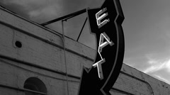 Retro neon EAT sign black and white Stock Footage