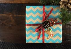 Festive Christmas gift box with chevron stripe wrapping on dark recycled wood Stock Photos