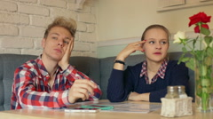 Irritated couple sitting in the cafe and waiting for their order - stock footage