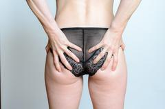 Woman in black lingerie clasping her bum - stock photo
