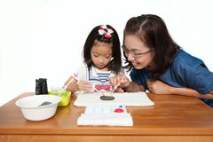 Stock Photo of Mother teach daughter to painting