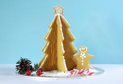 Christmas holiday gingerbread man and tree against pale blue and white backgr - stock photo