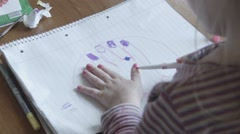 The girl draws an own hand on paper Stock Footage