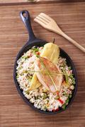 Fried rice and roast chicken breast in a skillet - stock photo