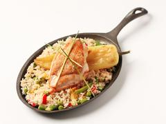 Fried rice and roasted chicken breast on a skillet - stock photo
