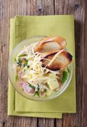Chicken or garlic soup with grated cheese and ham Stock Photos