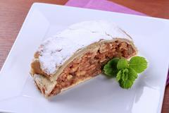 Slice of apple strudel powdered with icing sugar - stock photo
