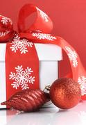 Festive red and white theme Christmas gift box on reflective white table agai Stock Photos