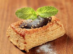 Chocolate filled puff pastry tart shell sprinkled with sesame seeds - stock photo