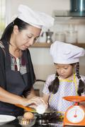 Mother and daughter using whisk to mix egg and wheat flour - stock photo
