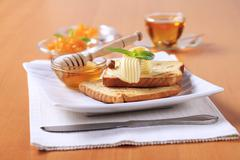 Breakfast - Toasted bread, butter, honey and marmalade - stock photo
