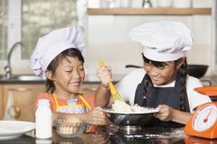 Little asian girls stiring wheat flour and egg - stock photo