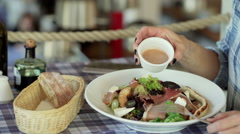 Woman sitting in the restaurant and eating a meal Stock Footage
