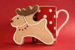 Reindeer vanilla cookie biscuit with red polka dot cup of coffee against a fe - stock photo