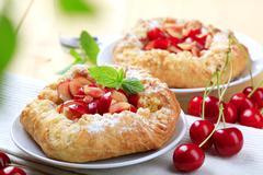 Crisp Danish pastries topped with fresh cherries - stock photo