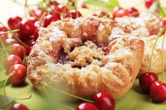 Danish pastry with jam filling and fresh cherries - stock photo