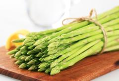 Bundle of Fresh asparagus shoots on a cutting board Stock Photos