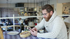 Happy man sitting in the restaurant and browsing internet on smartphone - stock footage