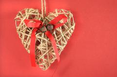 Festive vintage Christmas natural rope heart decoration on red background wit - stock photo