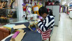 Girl in glasses cuts out a template pattern of cardboard, Yongle Fabric Market Stock Footage