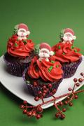 Three Christmas Cupcakes in purple polka dot wrapper with red frosting and sa - stock photo