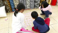 Children play mahjong cards sit on floor at Yongle Fabric Market Stock Footage