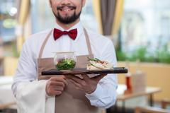 Cheerful male cafe worker is serving supper - stock photo