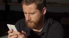 Man face with ginger beard looking absorbed and browsing internet on smartphone Stock Footage
