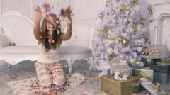 Beautiful girl throws up confetti near the Christmas tree in Slow Motion Stock Footage