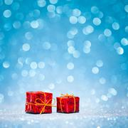 Red box with christmas gift on shiny glitter blue background Stock Photos