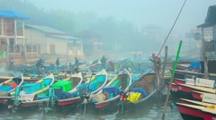 Long wooden motor boats parked near river bank covered by early morning fog Stock Footage
