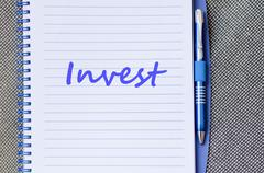 Invest write on notebook - stock photo
