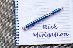 Risk mitigation write on notebook - stock photo