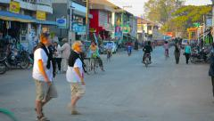 Motorbike, bicycle and people traffic on wide burmese small tourist town road Stock Footage