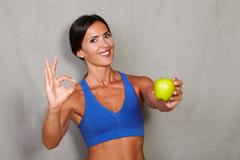 Satisfied lady showing apple and ok sign in fitness sport wear on grey textur Stock Photos