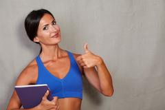 Healthy lifestyle female in fitness clothing showing ok sign and carrying tab Stock Photos