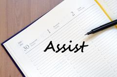 Assist write on notebook - stock photo