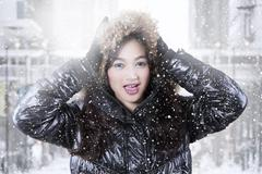 Stock Photo of Beautiful girl with winter jacket and snowfall