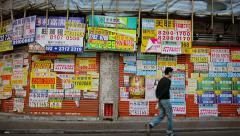 Man pass wall covered by many notices and announcement placard and posters Stock Footage