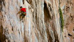 Rock climber climb up limestone cliff in safety belt on a rope Stock Footage
