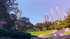 Petronas Twin Towers vies from green KL central city park with fountain Stock Footage