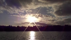 Sunshine Clouds Over Tree Topped Glistening Lake - Timelapse - stock footage