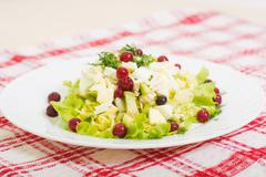 dietary salad from avocado, eggs, and cowberry on red tablecloth - stock photo