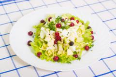 Stock Photo of dietary salad from avocado, eggs, and cowberry on blue tableclot