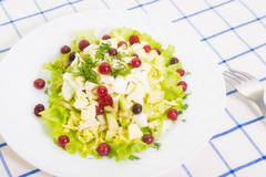 dietary salad from avocado, eggs, and cowberry on blue tableclot - stock photo