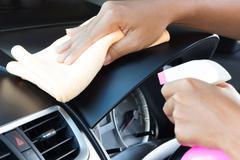 Closeup hand cleansing car dashboard Stock Photos