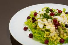 dietary salad from avocado, eggs, and cowberry on dark glass tab - stock photo