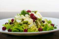 Dietary salad from avocado, eggs, and cowberry on dark glass tab Stock Photos